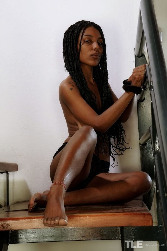 Knappe donkere vrouw vastgeketend aan de trap